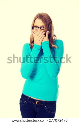 Teenage woman covering mouth because of shame - stock photo