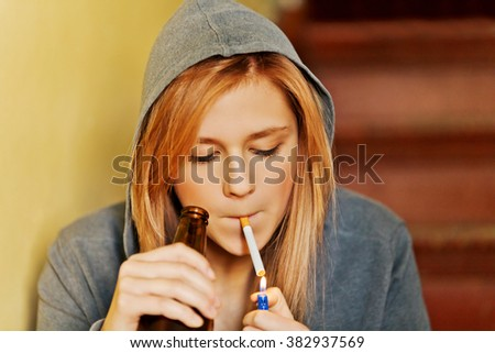 Teenage woman drinking beer and smoking cigarette - stock photo