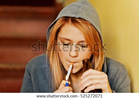 Teenage woman drinking beer and smoking cigarette.