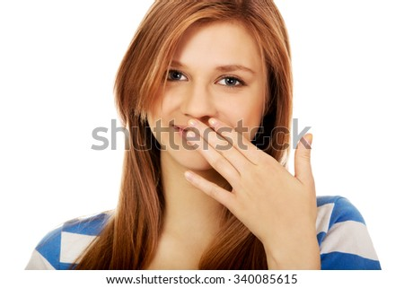 Teenage woman giggles covering her mouth with hand. - stock photo