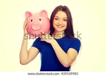 Teenage woman holding piggy bank. - stock photo