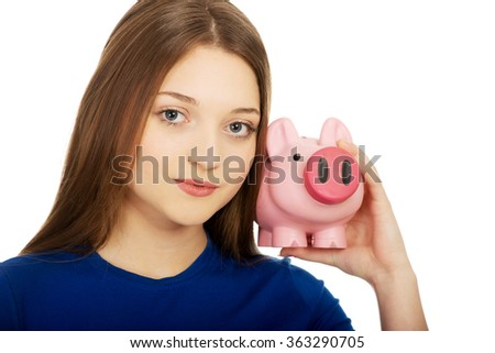Teenage woman holding piggybank. - stock photo