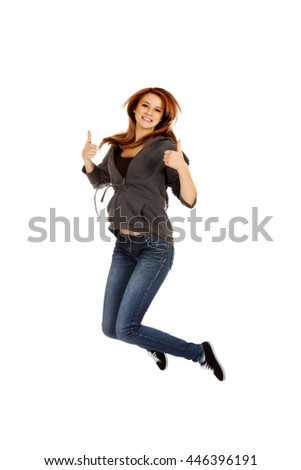 Teenage woman jumping showing thumbs up - stock photo