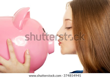Teenage woman kissing piggybank. - stock photo
