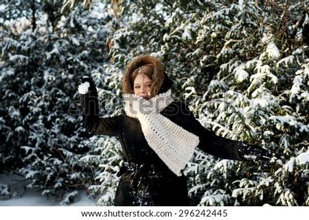 Teenage woman playing snowball fight - stock photo