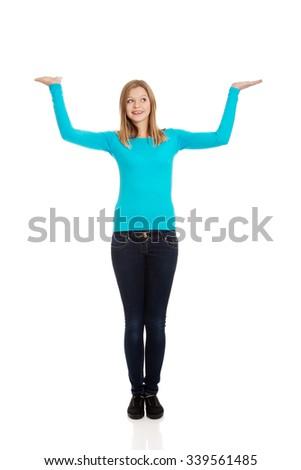 Teenage woman presenting something on both palms - stock photo