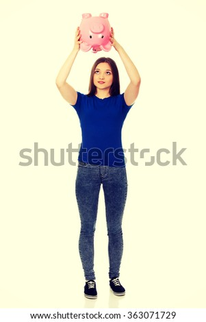 Teenage woman shaking piggybank. - stock photo