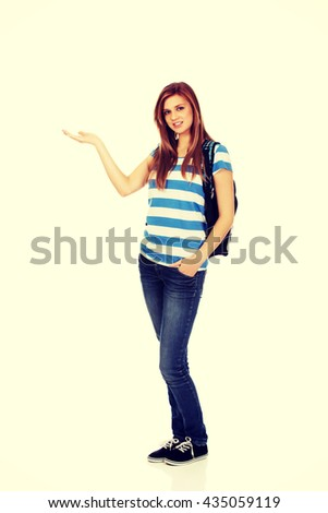 Teenage woman showing something on open palm - stock photo