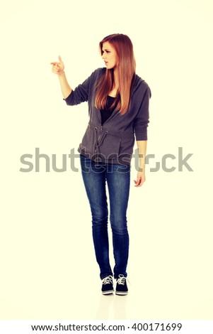 Teenage woman threatens someone the finger - stock photo