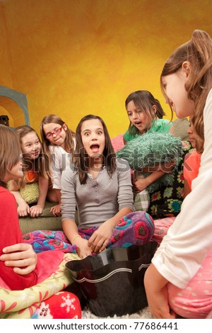 Teenaged girl tells a story at a sleepover - stock photo