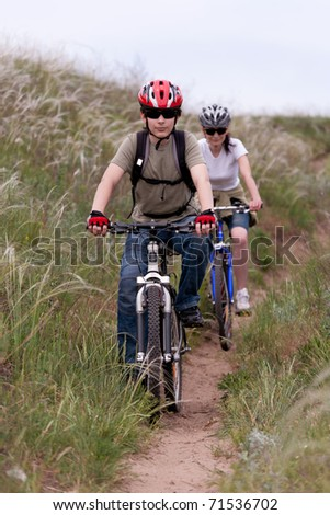 teenager and young woman on the mountain bike - stock photo