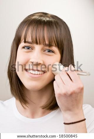 Teenager applying blush with makeup brush - stock photo