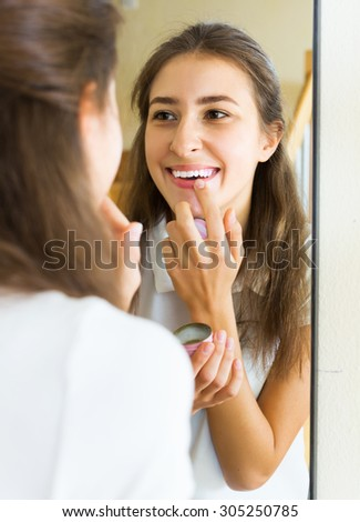 Teenager applying lipstick in front of a mirror at home - stock photo