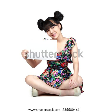 Teenager asian girl sitting on floor holding blank paper for advertisment with cheerful expression, Isolated over white - stock photo