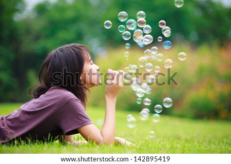 Teenager asian girl with soap bubbles in the park - stock photo