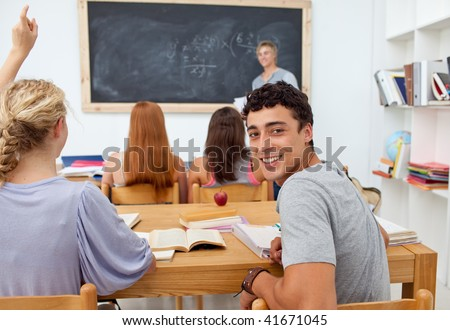 Teenager asking a question to a friend in the class - stock photo