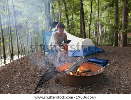 teenager at campsite with tent and camp fire - stock photo