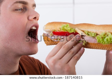 Teenager biting submarine sandwich with ham and vegetables
