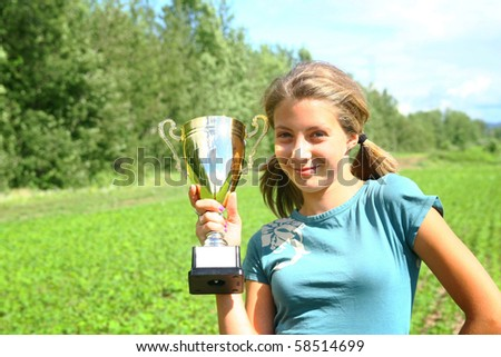 Teenager blond girl with a trophy in hand