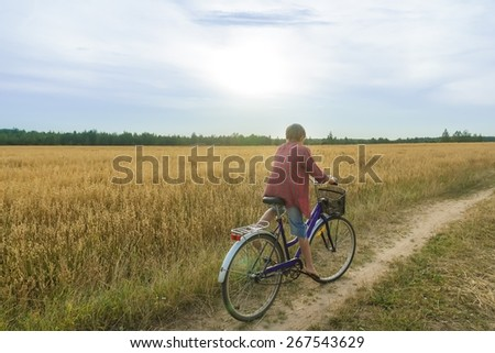 Teenager boy are cycling on dirt summer country road in cereal field back view  - stock photo