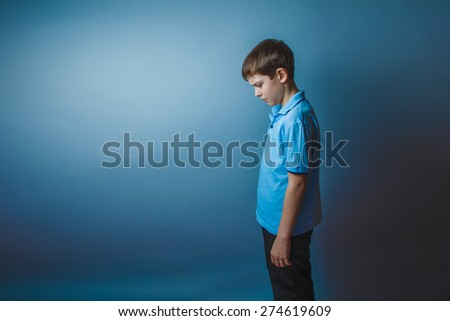 teenager boy Brown European appearance in a blue shirt stands sideways lowered his head on a gray background, sadness - stock photo