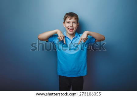 teenager boy brown European appearance in blue t-shirt showing thumbs down on a gray background, fun - stock photo