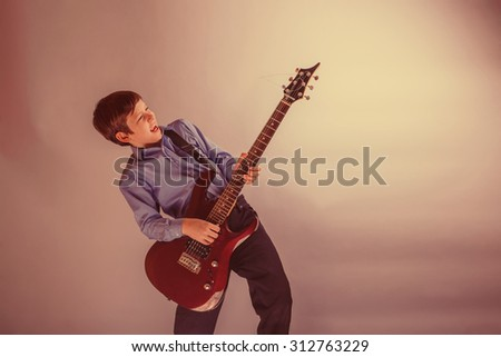 teenager boy brown hair European appearance playing guitar on a gray background retro - stock photo