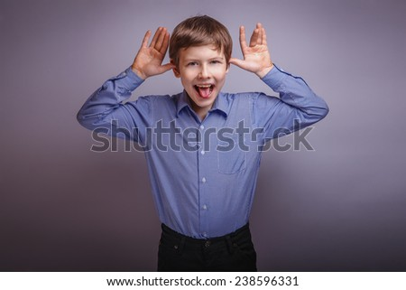 teenager boy brown hair of European appearance grimaces experiencing joy on a gray background