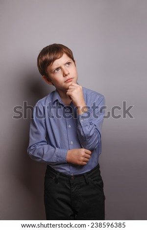 teenager boy brown hair of European appearance holds a hand under his chin deep in thought on a gray background - stock photo