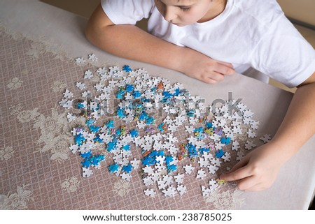 Teenager boy collects puzzles at the table - stock photo