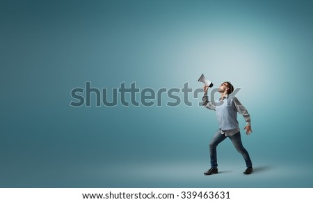 Teenager boy in glasses screaming emotional in megaphone - stock photo