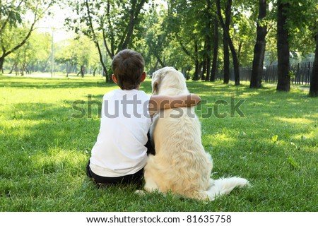 Teenager boy in the park with a golden retriever dog - stock photo
