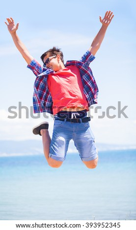 teenager boy  jumping happy in the beach with a blue sky in the background - stock photo