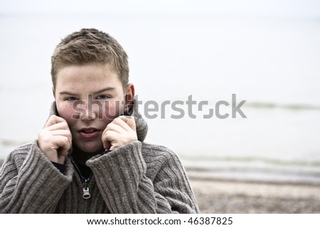 Teenager boy looking at camera in cold weather with sweater look for more o the same model