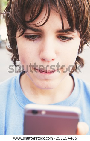 teenager boy looking in to the  smartphone on street - stock photo