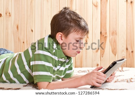 teenager boy lying on the bed with a Tablet PC