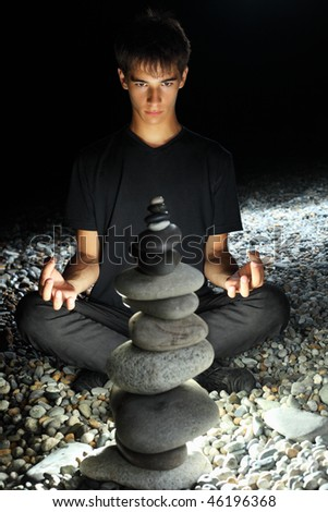 teenager boy meditating near pyramid from pebble on stony seacoast at night - stock photo