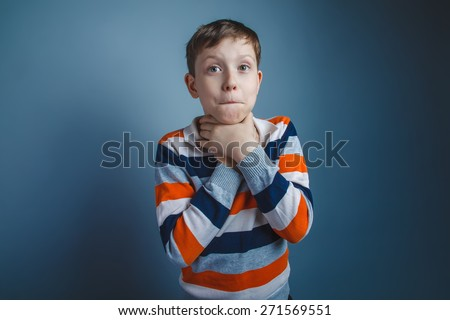 teenager boy of about ten European appearance brown hair holding hands by the throat on a gray background, choking - stock photo