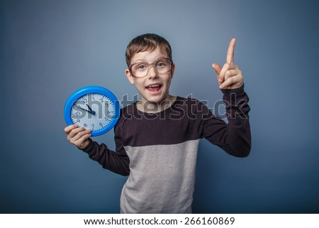 teenager boy of European appearance with glasses holding a blue clock lifted a finger up opened his mouth on a gray background, the opening time