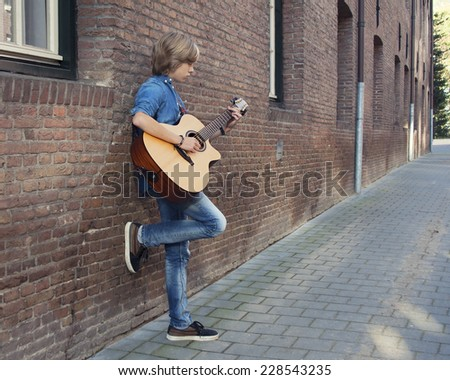 Teenager boy playing acoustic guitar outside on the streets - stock photo