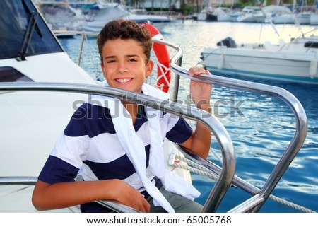 teenager boy sea marina summer vacation sitting in boat bow as sailor - stock photo