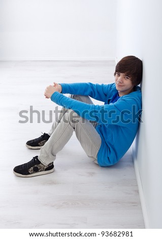 Teenager boy sitting by the wall in empty room - stock photo