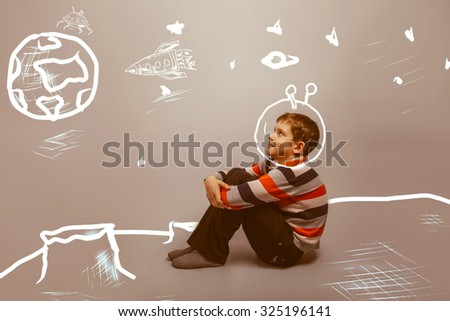 teenager boy sitting on the moon astronaut in space planet earth seen infographics childhood and dreams retro - stock photo