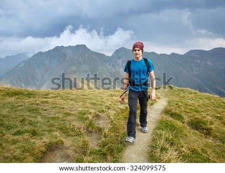Teenager boy with backpack hiking on a mountain trail