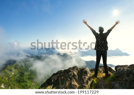 Teenager boy with backpack standing on top of a mountain with raised hands - stock photo