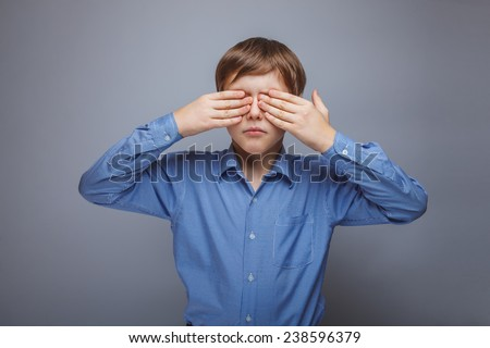 teenager boy 10 years brown hair Caucasian appearance eyes closed hands on a gray background - stock photo