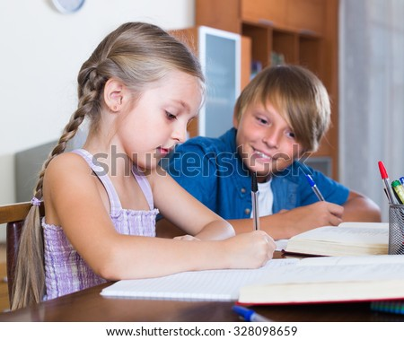 Teenager brother and cute little sister studying with books indoors