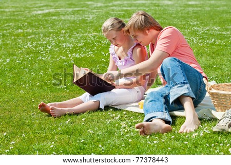 Teenager brother and sister having a picnic in the park in a bright sunny day
