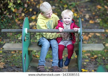 Teenager brother with toddler sister having fun on the playground - stock photo