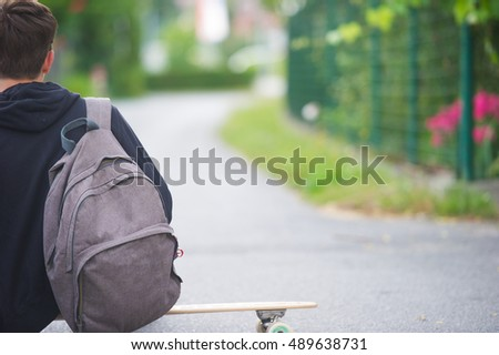 Teenager casually sitting on a longboard wearing his school backpack.